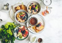 An overhead shot of a waffle, bowls of fruit oatmeal and a cup of coffee. Photo by Brooke Lark on Unsplash