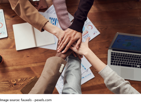 A group of people putting hands together at a workplace