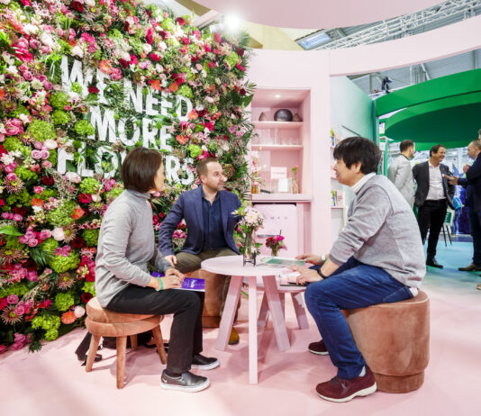 An image of IPM Essen 2020, three persons sitting in a table at a flower wall with the description in it: We need more flowers