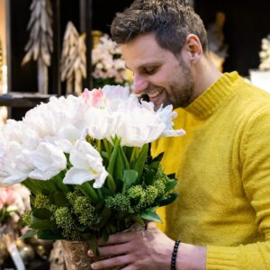 Floradecora trade fair. An image of a man smelling a bucket of flowers.